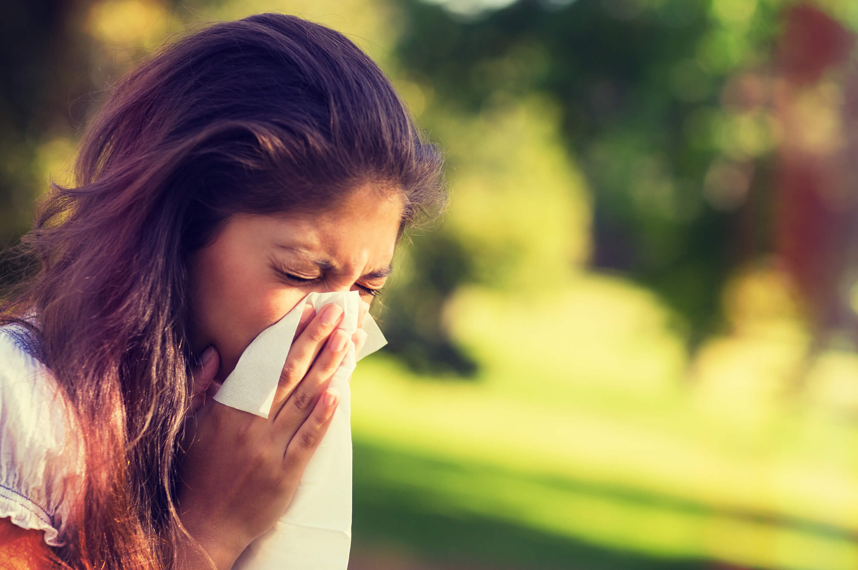 A woman experiencing nasal allergies outdoors.