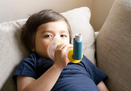 Young boy in New Orleans with inhaler for asthma