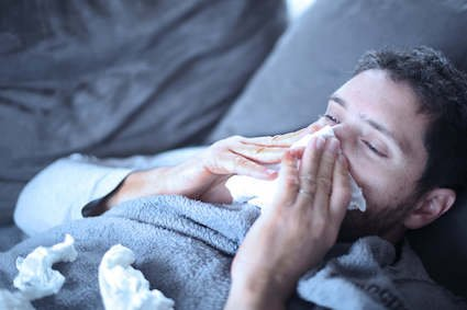 Man with sinusitis laying down and blowing his nose